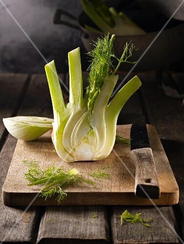 Fresh fennel, halved, on a wooden chopping board