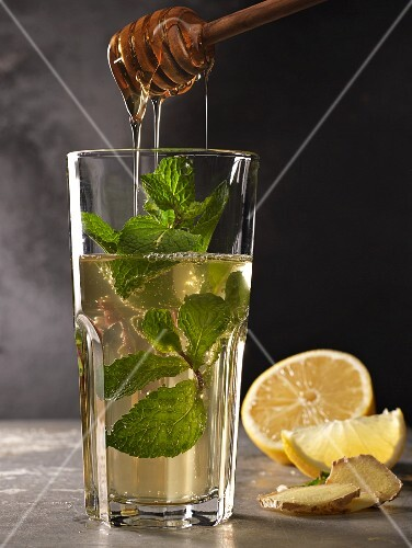 Mint tea in a glass with mint sprigs, lemon, ginger and honey