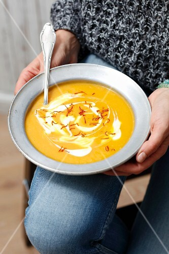 A woman holding a plate of cream of pumpkin soup