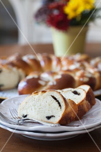 An bread wreath with poppyseeds and flaked almonds on a kitchen table