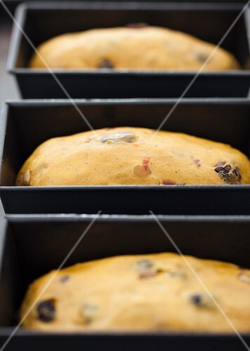 Dough for pumpkin bread with raisins, dried cherries and pumpkin seeds in loaf tins