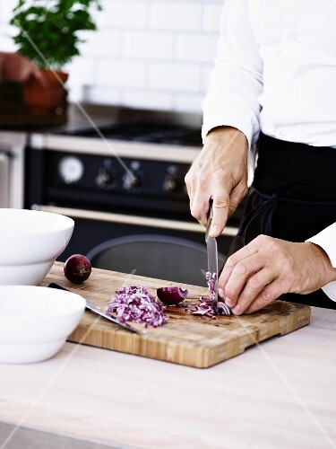 A man chopping onions on a wooden board in a kitchen