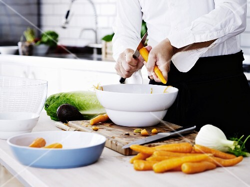 A man peeling carrots into a bowl in a kitchen