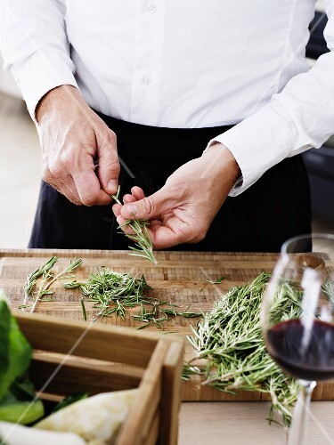 A man stripping needles off rosemary sprigs