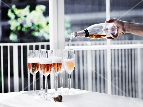 A person pouring Prosecco Rose into glasses