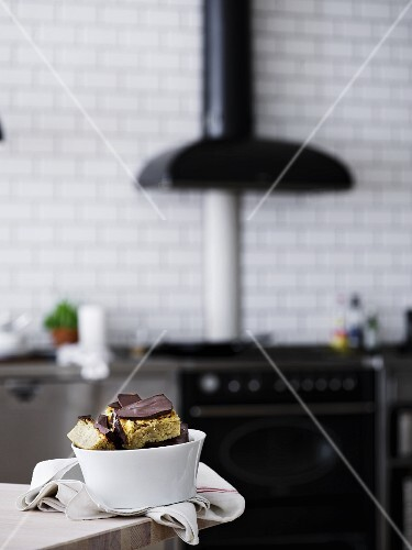 Slices of tray bake cake in a porcelain bowl on a table in a kitchen
