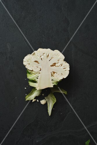 Half a cauliflower floret on a black slate surface