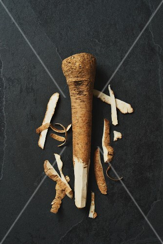 A horseradish root on a grey surface, partially peeled