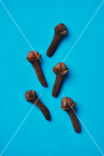 Five cloves on a blue surface (seen from above)