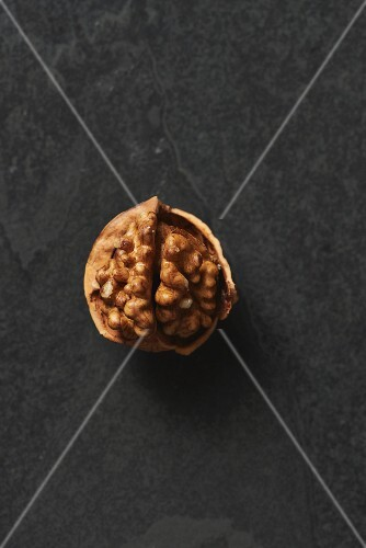 An opened walnuts on a grey surface (seen from above)