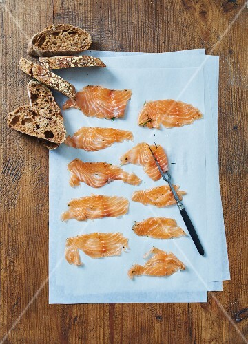 Homemade cured salmon on a piece of paper with slices of bread (seen from above)