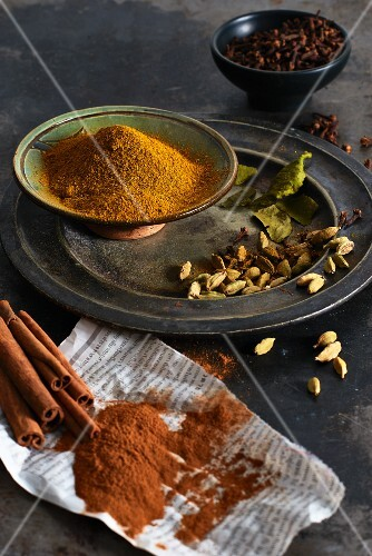 Various spices on a plate and on a piece of newspaper (whole and ground)