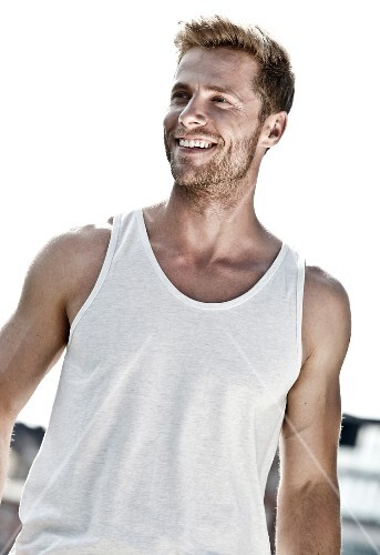 An athletic man with a three-day beard wearing a vest