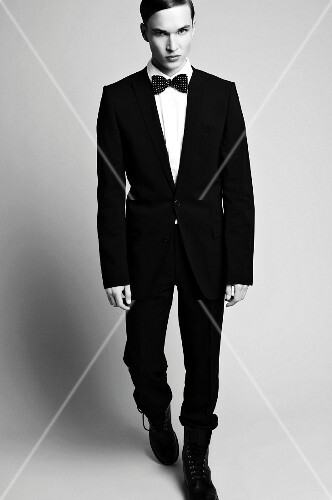 A young man wearing a black suit, a white shirt, a bow tie and lace-up boots (black-and-white shot)