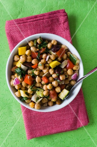A chickpea salad on a green surface