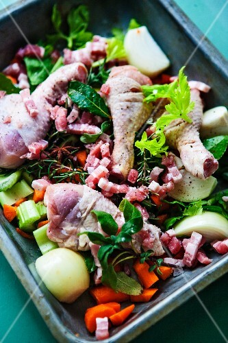 Ingredients for sauce (chicken, bacon and vegetables) in a roasting tin