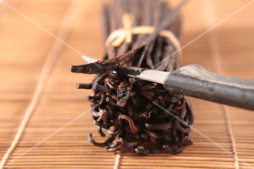 A bundle of vanilla pods with one slit open
