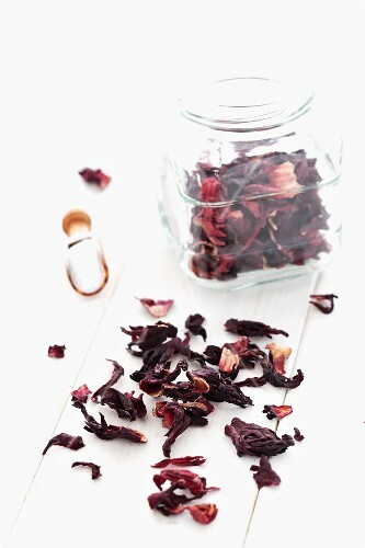 Dried hibiscus flowers in a jar and on a white cloth