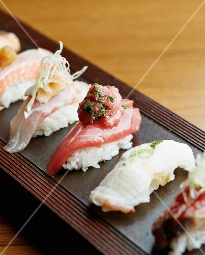 Various nigiri sushi on a wooden board