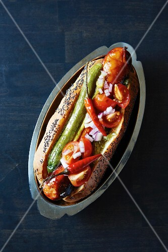 A hot dog with tomato salad and chilli peppers