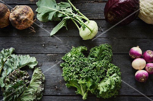 Various types of cabbages on a grey wooden table