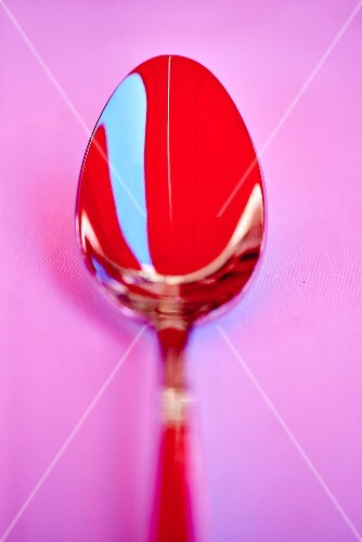 A red spoon on a pink surface