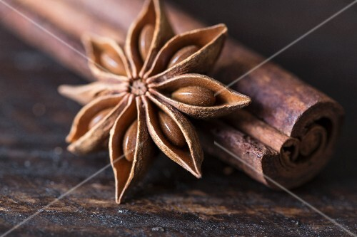Star anise and cinnamon sticks on a wooden surface