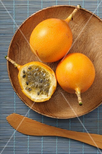 Yellow passion fruits, whole and halved, on a wooden plate