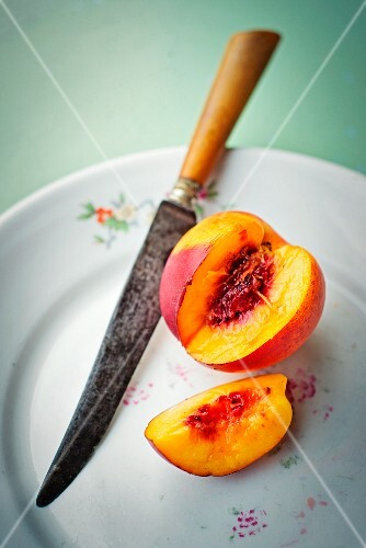 A nectarine, sliced, on a plate with a knife
