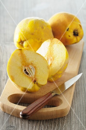 Quinces, whole and halved, on a chopping board with a knife