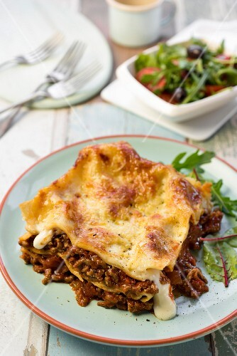 A portion of lasagne with salad