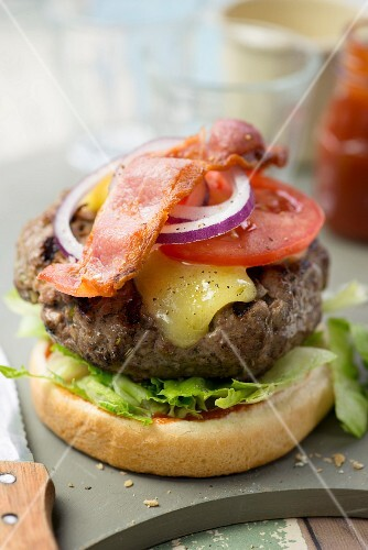 A beef burger with tomatoes and bacon