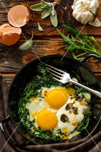Fried eggs with rocket, yoghurt and chilli