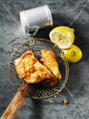 Fried halibut on a draining spoon