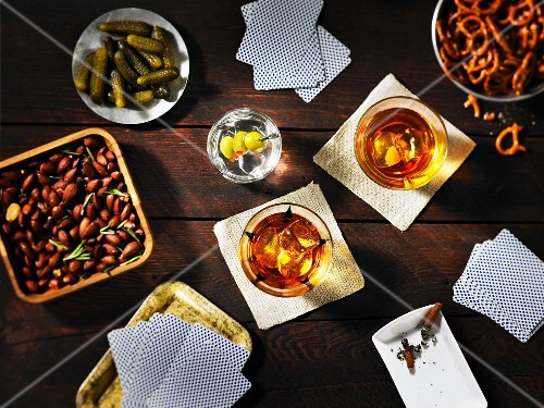 Guys night: playing cards, drinks and snacks on a table (seen from above)