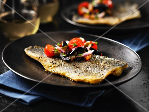Fried seabass with tomatoes and olives