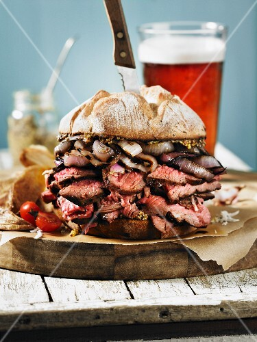 A giant steak sandwich on a wooden board with a beer