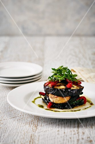 A stack of vegetables with aubergines, peppers and rocket