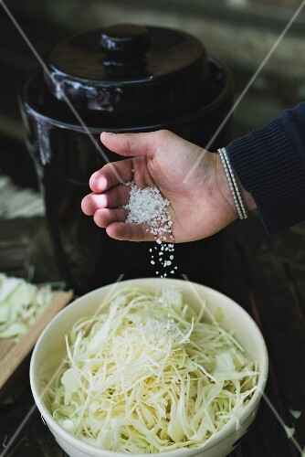 Salt being added to grated white cabbage