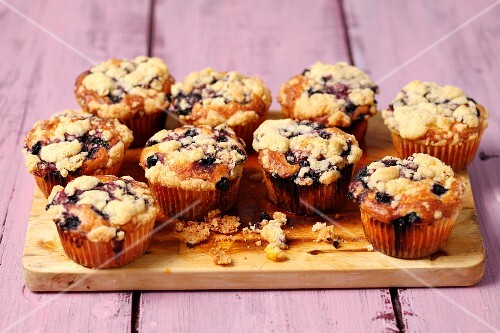 Yoghurt cupcakes with blueberries and crumbles on a wooden board