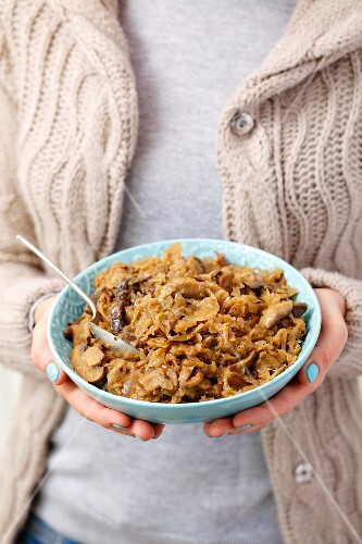 A woman holding a bowl of braised sauerkraut with mushrooms