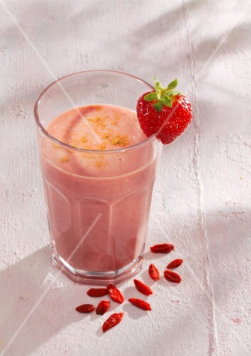 A strawberry and coconut smoothie with coconut milk and goji berries