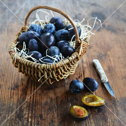 Plums in a rustic basket and next to it