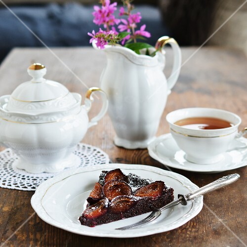 A slice of chocolate cake with plums and icing sugar served with tea