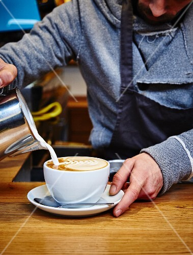 A barista pouring milk foam into a coffee cup