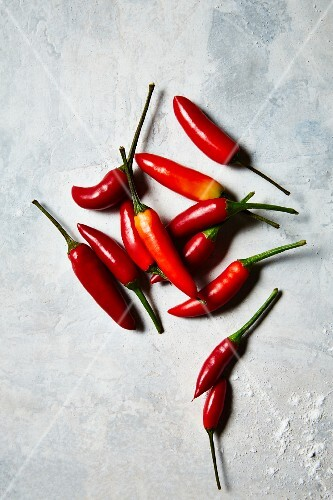 Red chilli peppers on a white surface (seen from above)