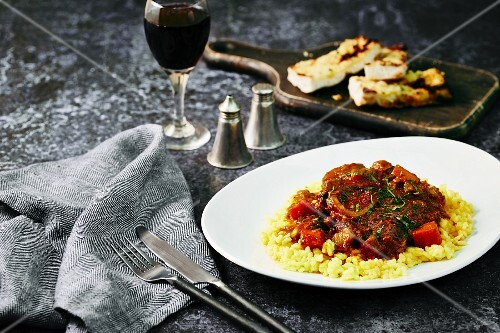 Osso bucco on a bed of risotto with garlic bread (Italy)