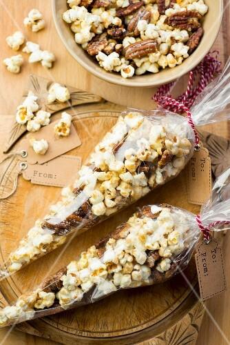 Karamellisiertes Popcorn mit gesalzenen Pecannüssen in Cellophantüten