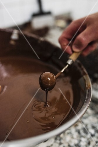 A praline being dipped into liquid chocolate