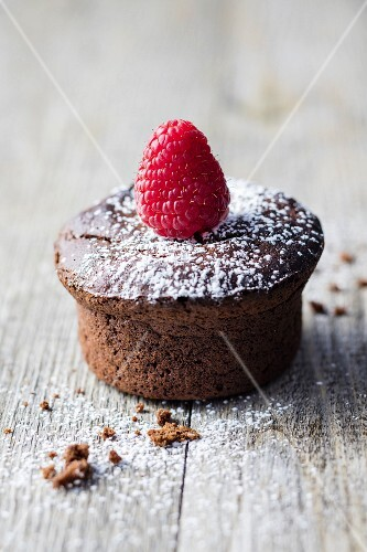 A gluten-free chocolate muffin decorated with a raspberry